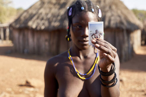 Mudimba tribe woman showing a picture of herself, Canhimei, Angola. - VEGF00544