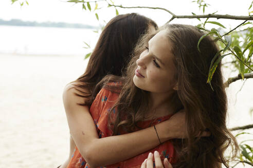 Teenage girls embarcing on beach - AMEF00063