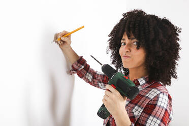 Woman using portable drill, marking with pencil on a wall - RTBF01347