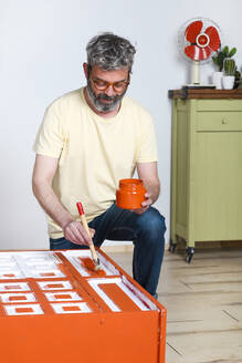 Man painting furniture with brush at home - RTBF01356