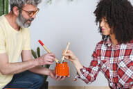 Couple using brushes and paint at home - RTBF01362