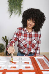 Woman painting furniture with brush at home - RTBF01365