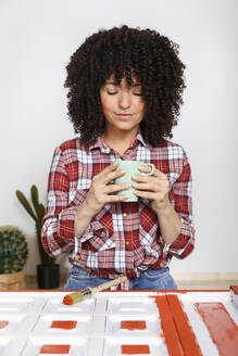 Woman holding cup of coffee at home, painted furniture - RTBF01371