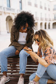 Multicultural happy women talking and using smartphone, sitting on bench - MPPF00014