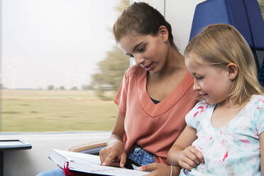 Two sisters sitting in a train, reading a book - FKF03602