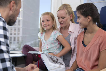 Family traveling by train, daughtres reading a book - FKF03608