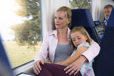 Daughter sleeping on mother's lap in a train - FKF03611