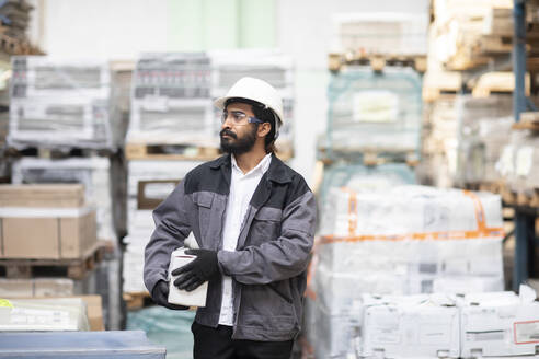 Young man wearing hard hat working in a warehouse carrying a box - SGF02417