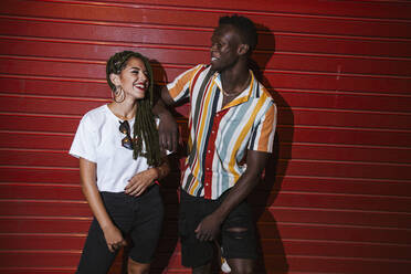 Happy young couple standing at red roller shutter at night - LJF00777
