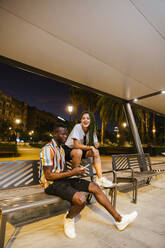 Cool young couple on a bench at night in the city - LJF00780
