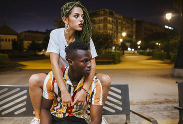 Cool young couple on a bench at night in the city - LJF00783