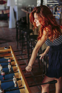 Young woman playing foosball in a sports bar - LJF00822