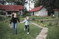 Carefree mother and daughter running in garden - KMKF01039