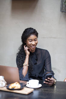 Smiling chic businesswoman using smartphone at table in a cafe - ALBF00985
