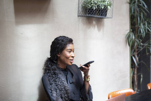 Smiling chic businesswoman using smartphone in a cafe - ALBF00988