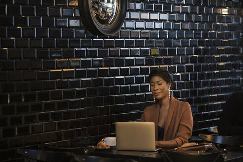 Chic businesswoman using laptop at table in a cafe - ALBF00994