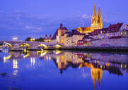 Stone bridge over Danube river in illuminated city at dusk, Regensburg, Upper Palatinate, Bavaria, Germany - SIEF08928