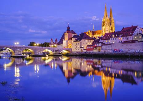 Stone bridge over Danube river in illuminated city at dusk, Regensburg, Upper Palatinate, Bavaria, Germany - SIEF08928