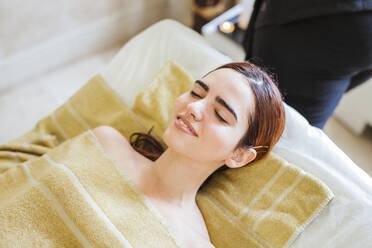 Relaxed young woman lying on massage lounge in a spa - LJF00859