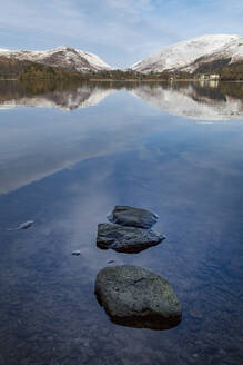 Stones in shallow water and perfect reflection of snow covered mountains and sky in the still waters of Grasmere, Lake District National Park, UNESCO World Heritage Site, Cumbria, England, United Kingdom, Europe - RHPLF04750