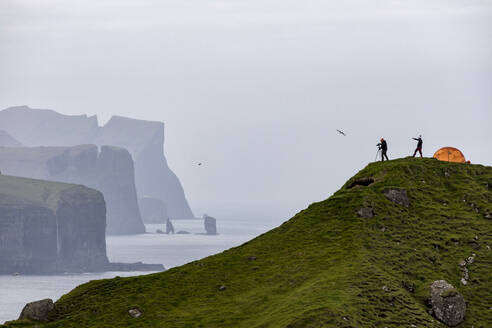 Hikers and tent on cliffs, Kalsoy Island, Faroe Islands, Denmark, Europe - RHPLF04834