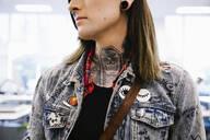 Student with tattoos on neck wearing denim jacket - HEROF37951