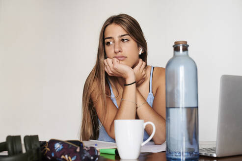 Female student studying at home, looking sad to the side - IGGF01298