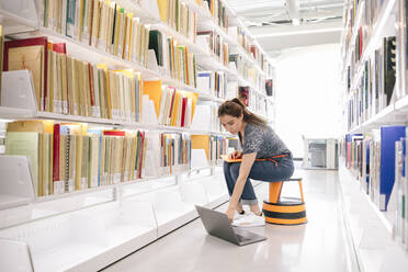 Student using laptop and looking for file on shelf in library - HEROF37983
