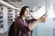 Student video calling on smartphone in library - HEROF38049