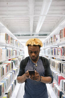 Student concentrating on smartphone in library - HEROF38061