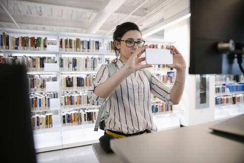 Student taking photo of library computer with smartphone - HEROF38091