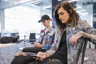 Students wearing denim jackets using smartphones - HEROF38157