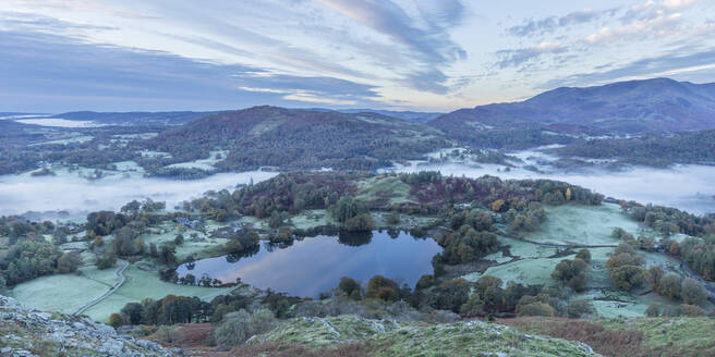 View of Loughrigg Tarn and early morning mists in autumn from Loughrigg Fell, Lake District National Park, UNESCO World Heritage Site, Cumbria, England, United Kingdom, Europe - RHPLF05854