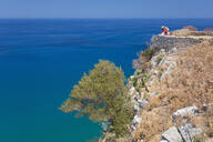 Lone visitor admiring view over the Tyrrhenian Sea from summit of La Rocca, Cefalu, Palermo, Sicily, Italy, Mediterranean, Europe - RHPLF05893