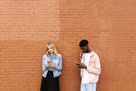 Young couple using smart phones against brick wall - HEROF38305