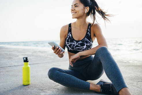 Woman using smartphone and in-ear during workout, sitting on a pier - OYF00009