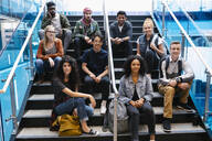 Portrait of university students sitting on staircase and looking at camera - HEROF38404