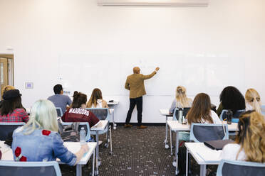 Male professor writing on whiteboard in university lecture - HEROF38446