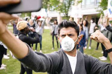Student protestor wearing pollution mask filming himself on smartphone - HEROF38473