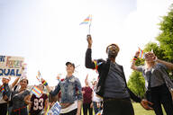 Students marching with rainbow flags at gay pride parade - HEROF38476