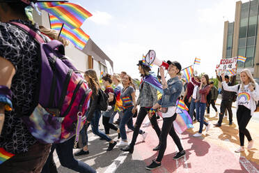 Group of students with rainbow flags and megaphone on gay pride march - HEROF38485