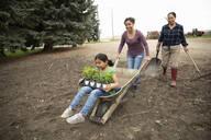 Multi-generation women gardening, pushing wheelbarrow - HEROF38530