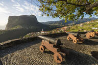 Historical cannons at Faial fortress with the village in the background, Faial, Santana municipality, Madeira, Portugal, Atlantic, Europe - RHPLF07020