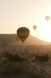 Silhouette hot air balloons flying over landscape against clear sky during sunset at Goreme National Park, Turkey - KNTF03276