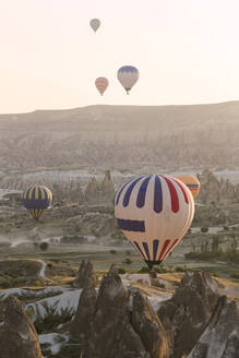 Colorful hot air balloons flying over land at Goreme National Park during sunset, Cappadocia, Turkey - KNTF03279