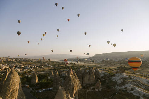 Colorful hot air balloons flying at Goreme National Park during sunset, Cappadocia, Turkey - KNTF03282
