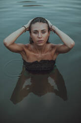 Portrait of young blond woman bathing in a lake - ACPF00625