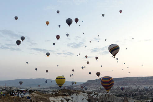 Colorful hot air balloons flying over landscape against sky in Turkey during sunset, Cappadocia - KNTF03289