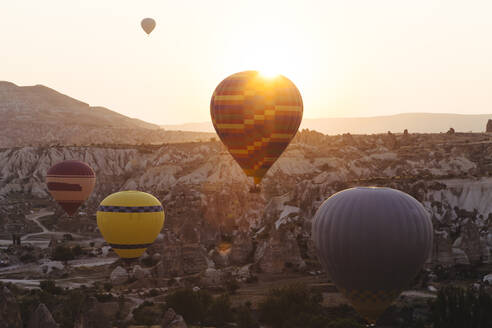 Colorful hot air balloons flying over rocky landscape in Goreme during sunset, Cappadocia, Turkey - KNTF03292
