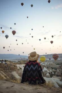 Young woman and hot air balloons in the evening, Goreme, Cappadocia, Turkey - KNTF03298